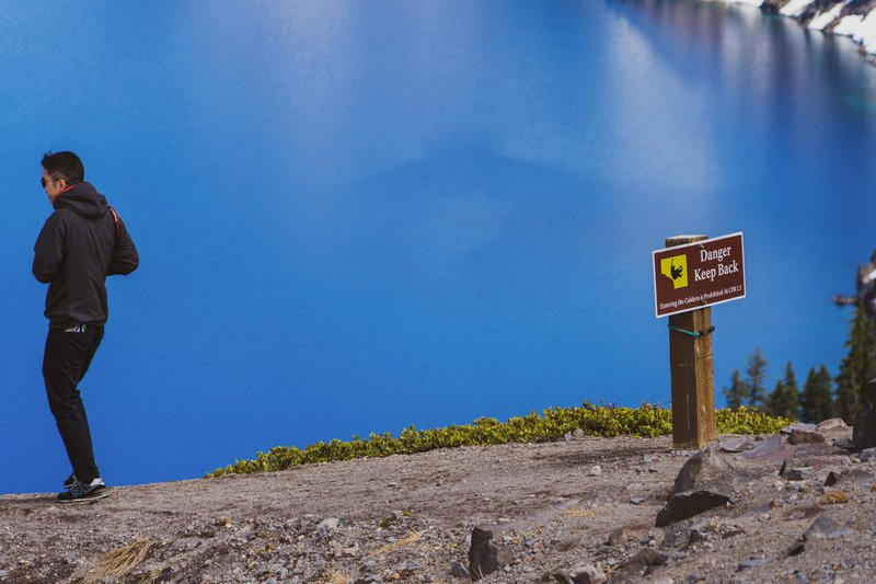 In this picture there's a sign and a person making a really poor decision. This guy ignored the signs at Crater Lake in Oregon and then nearly fell as he tried to get closer to the edge to take photos. That shortly after a couple nearly fell trying to take a selfie. I'm amazed more people don't fall to their deaths at crater lake... the guy in this picture was caught and then chewed out royally by a park ranger.